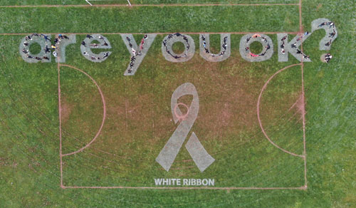 Students spell out Are You OK on the sports field